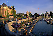 Empress Hotel, Parliament Building and Inner Harbour with people walking on promenade; Victoria, Vancouver Island, British Columbia, Canada.