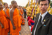 "01 FEBRUARY 2013 - PHNOM PENH, CAMBODIA:   Cambodian security officer (right) with Buddhist monks at the funeral procession of former King Norodom Sihanouk. Norodom Sihanouk (31 October 1922 - 15 October 2012) was the King of Cambodia from 1941 to 1955 and again from 1993 to 2004. He was the effective ruler of Cambodia from 1953 to 1970. After his second abdication in 2004, he was given the honorific of ""The King-Father of Cambodia."" Sihanouk died in Beijing, China, where he was receiving medical care, on Oct. 15, 2012. His cremation is will be on Feb. 4, 2013. Over a million people are expected to attend the service.  PHOTO BY JACK KURTZ"