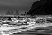 Basalt sea stacks tower off the coast of Iceland as ocean waves break on Black Sand Beach.