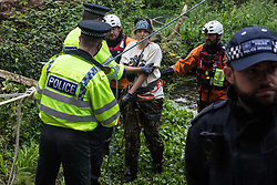 Denham, UK. 24 July, 2020. Swan, an environmental activist from HS2 Rebellion, is arrested by Metropolitan Police officers following her removal after almost fourteen hours from a line above the river Colne attached to an ancient alder tree which she had been seeking to protect from destruction during works for the HS2 high-speed rail link. A large policing operation involving the Metropolitan Police, City of London Police, Thames Valley Police and Hampshire Police as well as the National Eviction Team ensured the removal of the tree.