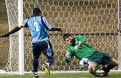 Virginia goalkeeper Dan Louisignau (18) makes a save as St. Peters forward Murphy Wiredu (7) approaches.  The Virginia Cavaliers defeated the Saint Peters Peacocks 3-1 in the first round of the NCAA Men's Soccer tournament held at Klockner Stadium in Charlottesville, VA on November 24, 2007.