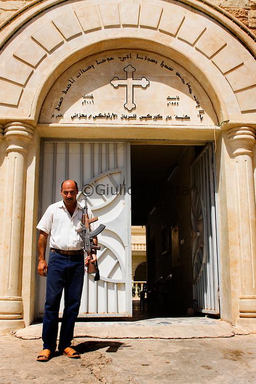 Bahzani, Mosul, Iraq: Armed guard in front of Saint George church in Bahzani, Mosul, Iraq
