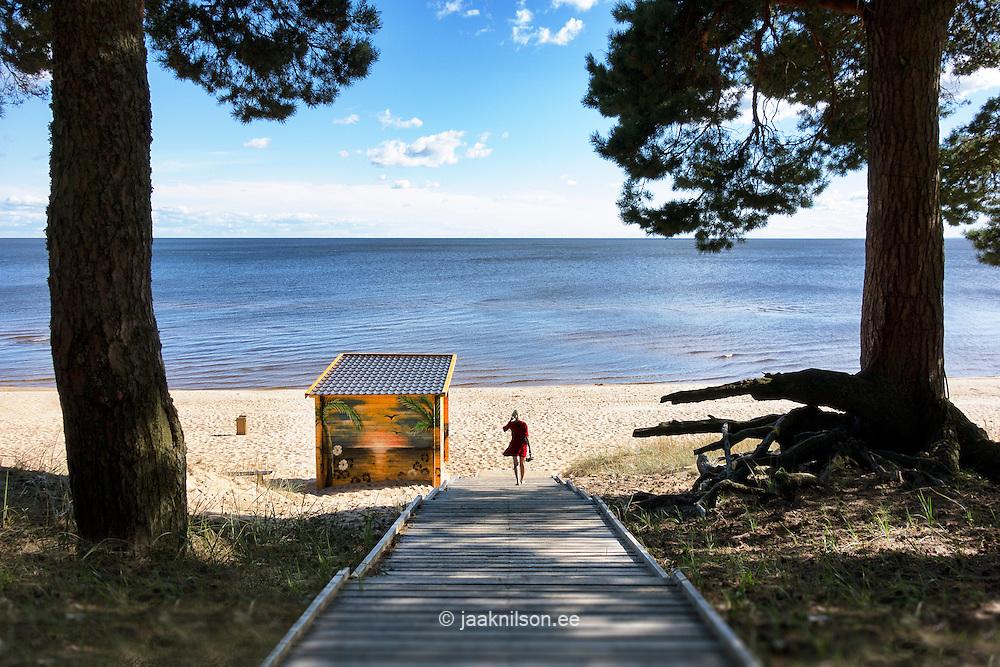Woman walking away on wooden boardwalk. Hilly sandy beach in Kauksi at Lake Peipsi, Estonia.