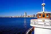 The Coronado Island ferry and the downtown towers across San Diego Harbor, San Diego, California USA
