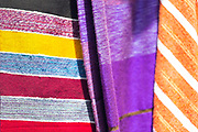CHEFCHAOUEN, MOROCCO - 27th APRIL 2016 -  Colourful textiles and materials hang for sale at a market stall in the Chefchaouen Medina - the blue city - Rif Mountains, Northern Morocco.