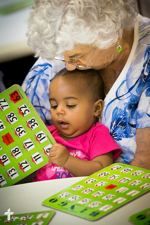 Resident Josephine Arkanoff holds Lylah St. Georges, daughter of Deaconess Alyssa St. Georges of Lutheran Church of the Redeemer, as the two play bingo with Y4Life student volunteers on Saturday, Sept. 12, 2015, in Sanford, Fla. LCMS Communications/Erik M. Lunsford