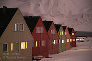 Colorful homes catch glow of rosy non-nacreous polar stratospheric clouds in the polar night of January in Longyearbyen, Svalbard, Norway.