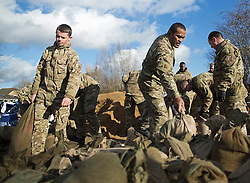 © London News Pictures. 11/02/2014. Wraysbury, UK. Soldiers from the 1st Battalion of the Royal Regiment of Fusiliers helping to move sandbags in Wraysbury, Surrey, one of the worst hit flood areas in the south east of England. The area has been hit hard by recent flooding from the nearby Thames River. Photo credit : Ben Cawthra/LNP