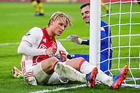 AMSTERDAM - Ajax - ADO , Voetbal , Eredivisie , Seizoen 2016/2017 , Amsterdam ArenA , 29-01-2017 ,  Ajax speler Kasper Dolberg scoort de 3-0 maar komt vervelend neer naast ADO Den Haag speler Ernestas Setkus (r) en blesseert zijn hand