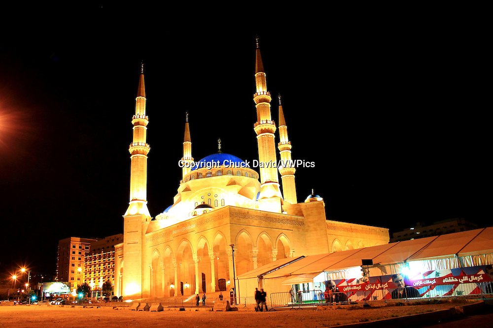 The brightly lit Al Amin mosque at night in Beirut, Lebanon, tents with political advertisements and images of Hariri and the Lebanese flag alongside it.