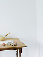 Bowl eggs and flour scattered on table