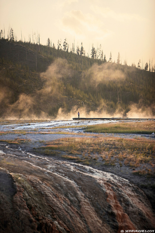 A solitary person stands in the mist at the Midway Geyser Basin in Yellowstone National Park during sunset.