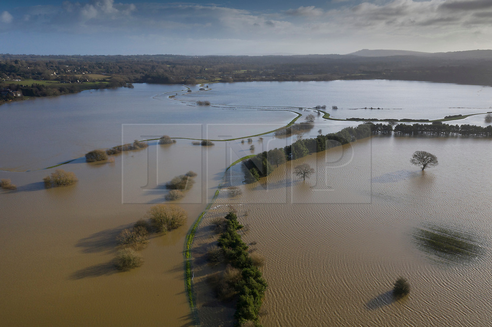 © Licensed to London News Pictures. 21/12/2019. Pulborough, UK. The outline of the of the River Arun can be seen in the flood water after it burst its banks and flooded local businesses and farm land. River levels remain high after heavy overnight rain in the south where more rain is expected today. Photo credit: Peter Macdiarmid/LNP
