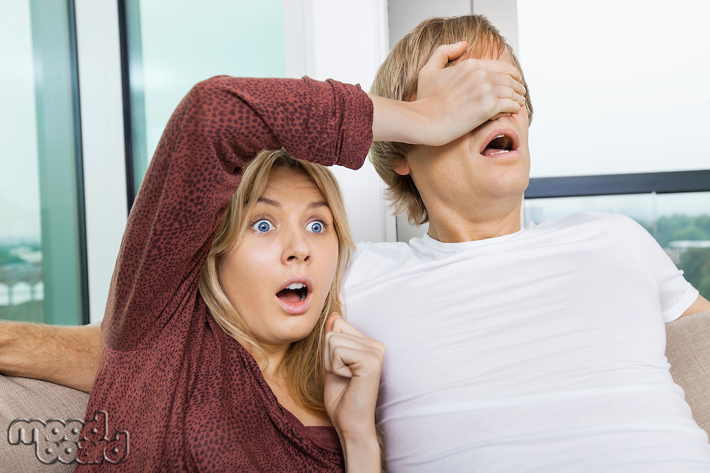 Shocked woman covering man's eyes while watching TV at home