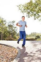 Full length of smiling man listening music while jogging in park