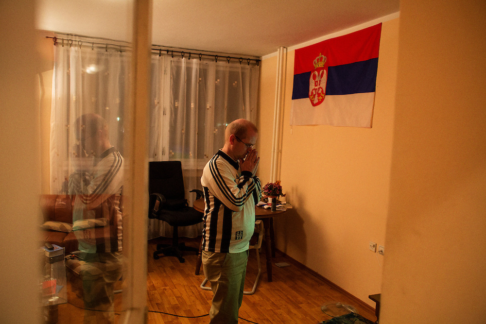 Norwegian writer Kristian Kahrs at home alone in his Belgrade apartment to watch his football team play in penultimate game of the year. Rosenborg lost 0-1 to Fredrickstad,..Photographed for Plot Magazine.