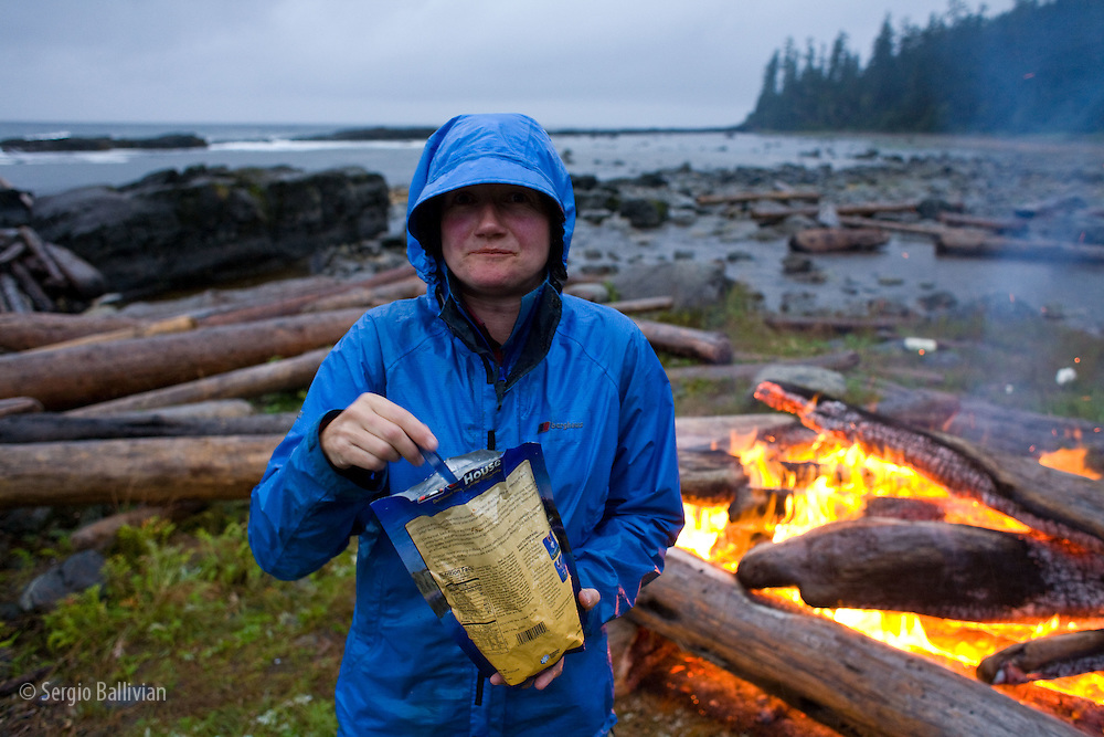 West Coast Trail - Day 4.  Wet and tired trekkers stand next to a large bonfire eating and drinking in a non-stop rainshower at Cribbs Creek.