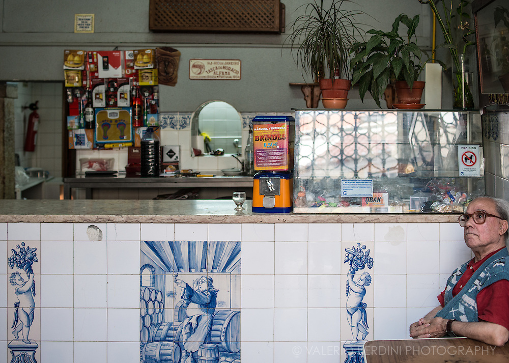 A man watches television in a cafe in Alfama. The bar is decorated with azulejos.