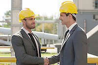 Young businessmen in hard hats shaking hands at construction site