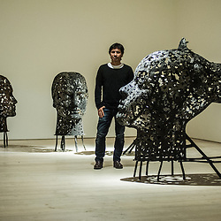London, UK - 2 September 2014: Artist Xavier Mascaró poses next to 'Head of Alexandra' (Right) and other iron portraits of a young woman from the Eleonora series reminiscent of the profiles on ancient coins. Xavier Mascaró's first UK solo exhibition will run from 3 September until 5 October at Saatchi Gallery.