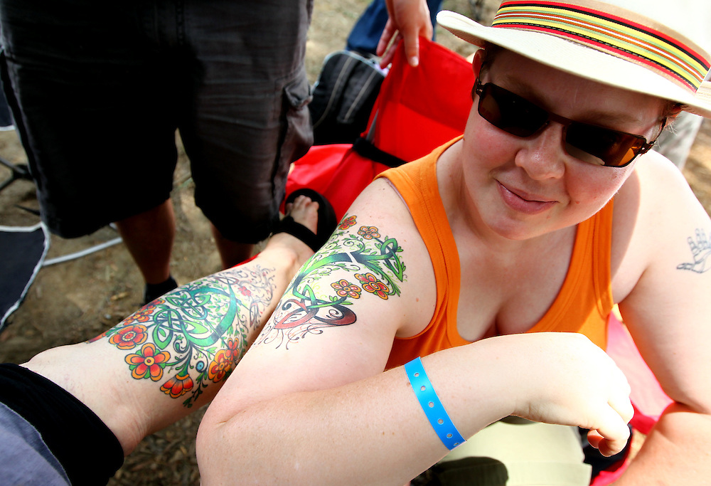 Rachel Swan (leg at left) and Karen Mattison show a friend their matching tattoos at the Wild Goose Festival at Shakori Hills in North Carolina June 25, 2011.  (Photo by Courtney Perry)