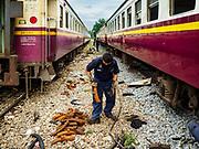 16 JULY 2018 - BANGKOK, THAILAND: Maintenance workers repair and clean third class train cars in the railroad yard at Thonburi train station in Bangkok.       PHOTO BY JACK KURTZ
