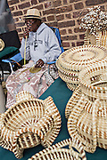 Gullah woman weaving sweetgrass baskets at the Historic Charleston City Market on Market Street in Charleston, SC.