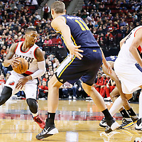 06 December 2013: Portland Trail Blazers point guard Damian Lillard (0) drives past Utah Jazz point guard Alec Burks (10) on a screen set by Portland Trail Blazers center Robin Lopez (42)  during the Portland Trail Blazers 130-98 victory over the Utah Jazz at the Moda Center, Portland, Oregon, USA.