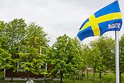 Svensk flagga med Sweden House-logga och falurött hus med vita knutar i bakgrunden, Sweden Hills, Japan.