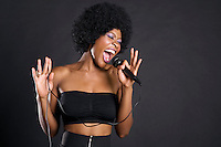 Woman singing on microphone over colored background