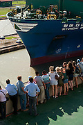 Tourists watching a containers cargo ship transit at Miraflores locks Visitors Center. Panama Canal, Panama City, Panama, Central America.