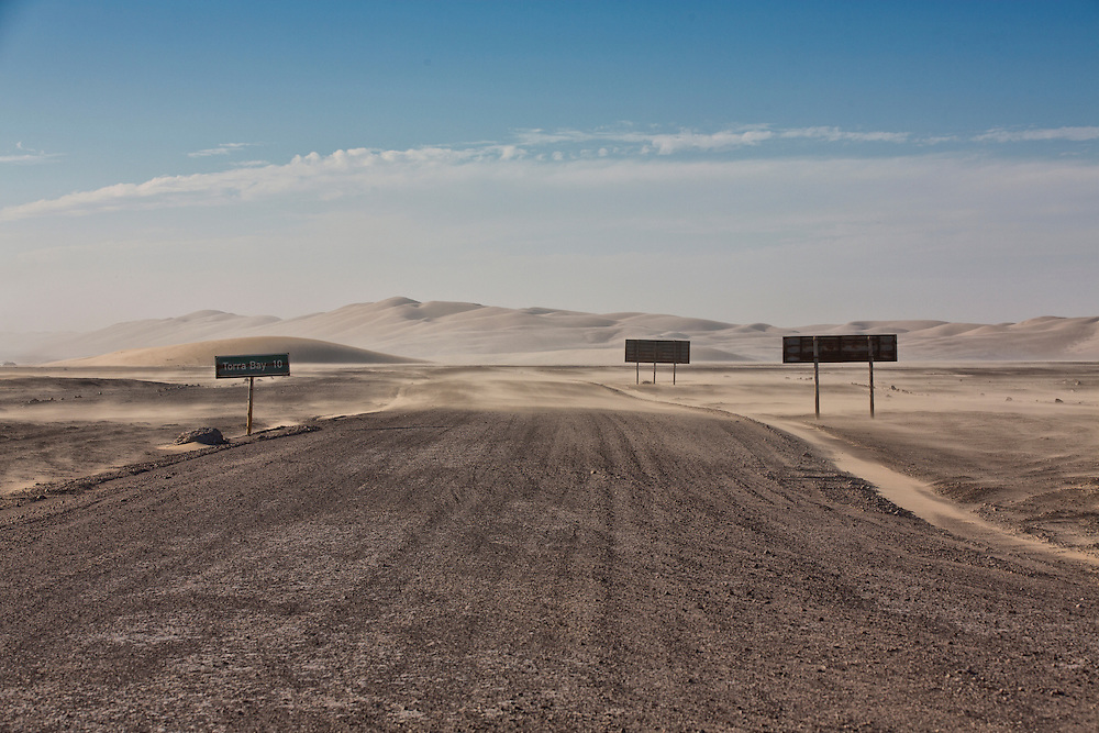 Sand blows across the Skeleton Coast Road at the Torra Bay intersection sign.
