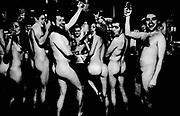 A group of naked drinkers in a pub raising a toast at the bar, UK 2004