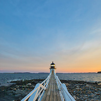 Maine photography of Marshall Point Lighthouse with its white wooden walkway, taken at sunset. This iconic New England lighthouse is located in Port Clyde, ME and marks the entrance to Port Clyde harbor.<br />
