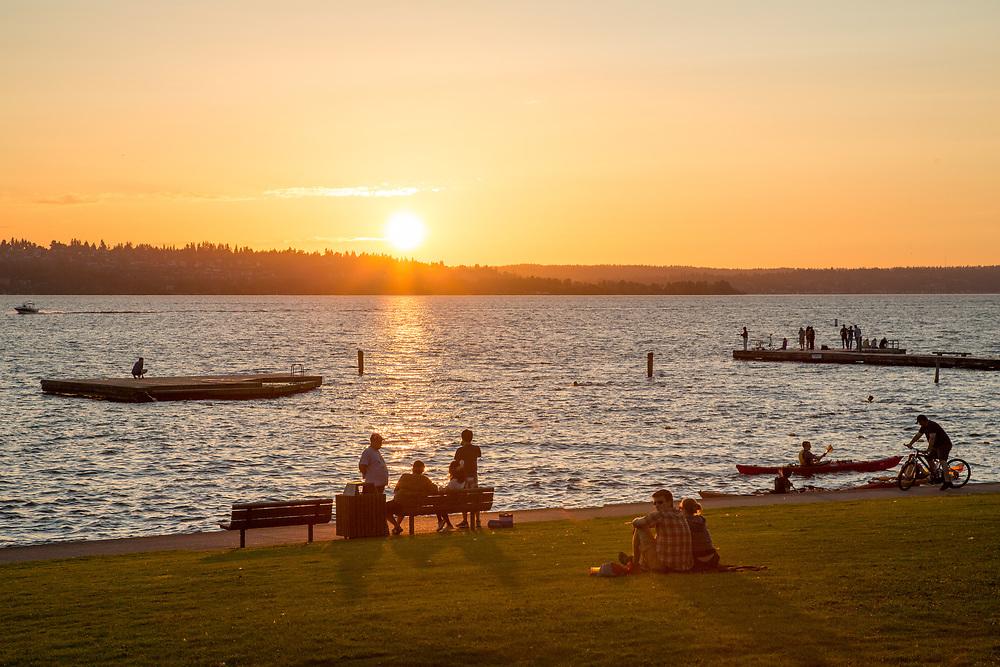 North America, United States, Washington, Kirkland, people at waterfront beach park on  Lake Washington at sunset.