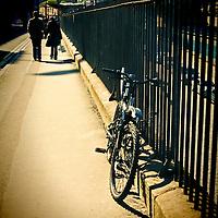 Couple walking along footpath in urban environment beside iron railings