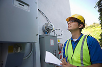 Maintenance worker reads meter of solar generation unit in Los Angeles California