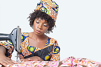 African American female fashion designer sewing fabric over gray background