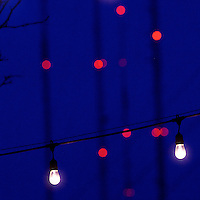 Porch lights dangle on wires with a complex of cell phone towers in the far distance December 16, 2016 in Philadelphia, PA.