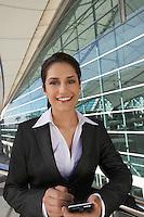 Businesswoman using PDA outdoors, portrait