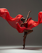 Contemporary female ballet dancer, Sadiya Ramos, with red flowy material, shot in the studio. Photograph taken in New York City by Rachel Neville.