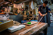 One of the tuna sellers cleans up his big knife after a day's work.