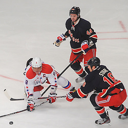 Washington Capitals left wing Alex Ovechkin (8) tries to make a play from his knees after being knocked to the ice by New York Rangers defenseman Steve Eminger (44) and defenseman Marc Staal (18) during first period NHL action between the Washington Capitals and the New York Rangers at Madison Square Garden in New York, N.Y.