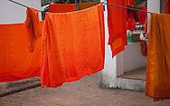 Orange clothes of monks drying on a washing rope.