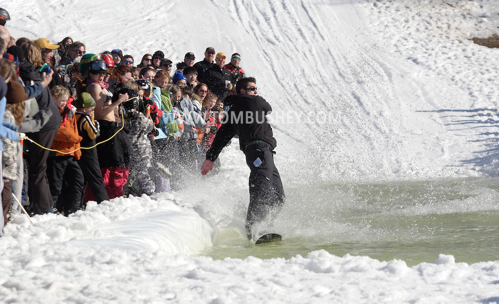 Warwick, NY - A snowboarder splashes the crowd while crossing the water at the end of a run during the Spring Rally at Mount Peter in Warwick on March 29, 2008.