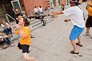 31 JULY 2010 - PHOENIX, AZ: Rev. SUSAN FREDERICK-GRAY, a Unitarian minister in Phoenix, dances the limbo in front of the 4th Ave Jail Saturday. Rev. Frederick-Gray was one of the 60 people arrested for blockading the Maricopa County Jail during protests this week. The last of the people arrested in Phoenix for protesting against Arizona's tough anti-illegal immigration law, SB 1070, were released from the 4th Ave Jail in Phoenix, AZ, Saturday morning. More than 60 people have been arrested for various charges related to peaceful protests that have been held across the city during marches and demonstrations against SB 1070 and Maricopa Sheriff Joe Arpaio's controversial crime sweeps which take place in heavily Hispanic neighborhoods.   Photo by Jack Kurtz