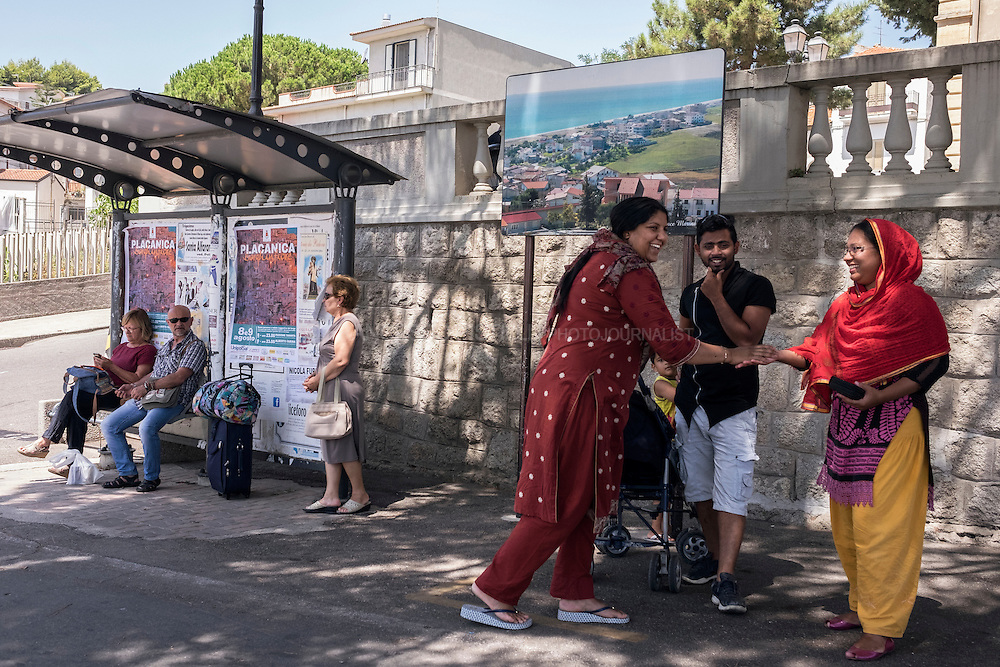 "A group of Bangladeshi refugees is chatting while waiting to take the bus to Riace Marina. There are few buses from and to Riace Marina, and this is a problem for whom is working or is looking for work in the ""marina"".  RIACE (ITALY) 01/08/16"