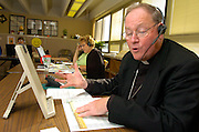 PLEASE DON'T HANG UP -- Archbishop Timothy M. Dolan of Milwaukee donned a telemarketer's headset Oct. 18 to help the Catholic Herald's telemarketing staff drum up subscriptions for his archdiocesan newspaper. Since the archdiocesan newspaper does not receive archdiocesan funding, nor does it have a mandatory parish subscription plan, it relies on telemarketers to replenish its subscription base. Archbishop Dolan volunteered to make a few telephone calls to help bring awareness to the need for more subscribers to his archdiocesan newspaper. (Catholic Herald photo by Sam Lucero)