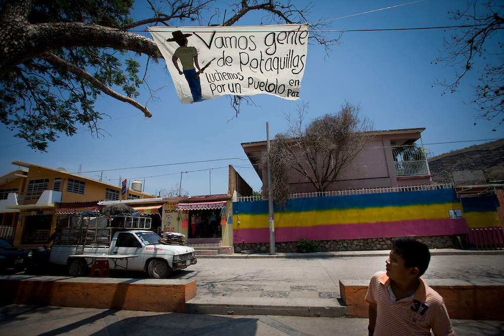 "A banner in the village reads ""lets go the people of Petaquillas to fight for a village in peace""."