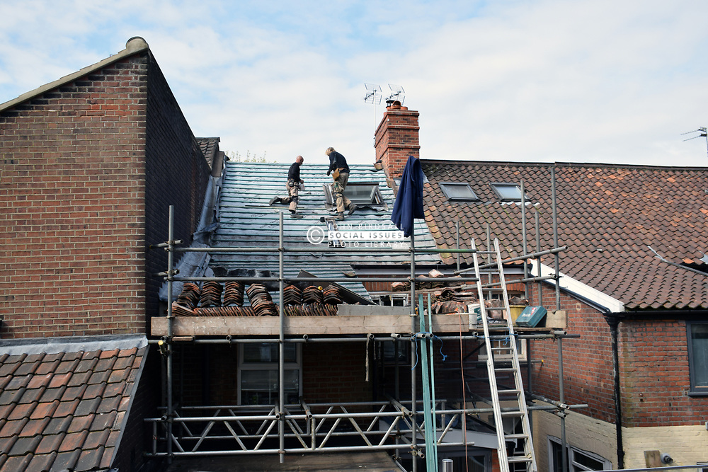 Roofers replacing felt on Victorian terraced house roof, Norwich UK